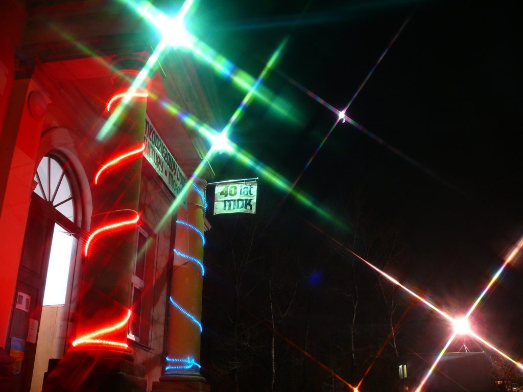 Budynek Młodzieżowego Domu Kultury przy ulicy Puławskiej 97. Wejście główne nocą z plakatem czterdziestolecie MDK